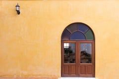 Hölzernes Fenster auf gelber Zementmörtelwand Lizenzfreie Stockbilder