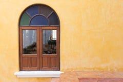 Hölzernes Fenster auf gelber Zementmörtelwand Lizenzfreies Stockbild