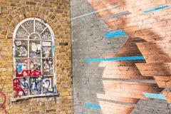 Hölzernes Fenster des klassischen Victorian auf einer Backsteinmauer bedeckt in den Gekritzeln Lizenzfreies Stockbild