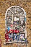 Hölzernes Fenster des klassischen Victorian auf einer Backsteinmauer bedeckt in den Gekritzeln Stockfotos