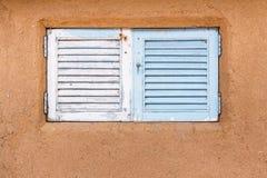 Hölzernes Fenster eingebettet in einer Schlamm- und Lehmwand Lizenzfreie Stockfotos