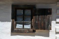 Hölzernes Fenster mit einem Fensterladen auf der weißen Wand stockbilder