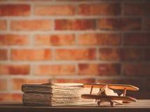 Hölzernes Flugzeugspielzeug der Weinlese und alte Bücher Lizenzfreies Stockbild