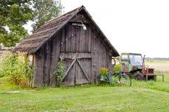 Hölzernes Gebäude des alten Bauernhofes und unterbrochener Traktor Stockbild