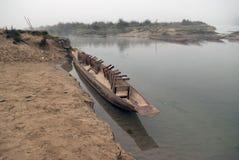 Hölzernes gebürtiges Kanu, mit umgekehrten Bänke für Sitz, nahe der sandigen Bank des Flusses, Chitwan, Nepal Lizenzfreie Stockbilder