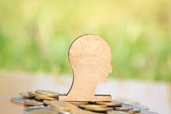 Hölzernes Gehirn und Stapel Münzen im Konzept von Einsparungen und von Geldwachsen oder von Energieabwehr stockfotografie