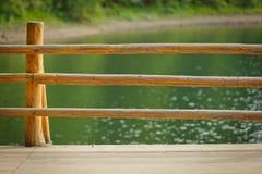 Hölzernes Geländer gegen blauen See Lizenzfreie Stockfotos
