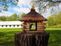 Hölzernes geschnitztes Vogelhaus auf einem Baumstumpf, eine Zufuhr für Vögel mit einer Taube in ihr stockfotografie