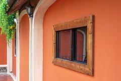 Hölzernes gestaltetes Fenster auf orange Wand lizenzfreies stockbild