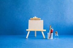 Hölzernes Gestell mit strukturiertem Segeltuch des leeren Papiers auf blauem Hintergrund Schöner Kunstunterrichtstudioinnenraum,  Stockbild