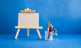 Hölzernes Gestell mit strukturiertem Segeltuch des leeren Papiers auf blauem Hintergrund Schöner Kunstunterrichtstudioinnenraum,  Lizenzfreie Stockbilder