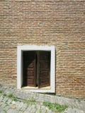 Hölzernes großes Fenster der Straße zum Haus des roten Backsteins stockbild