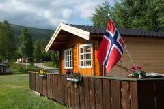 Hölzernes Häuschen mit norwegischer Flagge, Norwegen Lizenzfreie Stockfotos