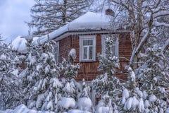 Hölzernes Häuschen schneebedeckt im Winter und in den Bäumen in den Schneefällen lizenzfreies stockfoto