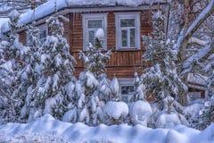 Hölzernes Häuschen schneebedeckt im Winter und in den Bäumen in den Schneefällen stockbild