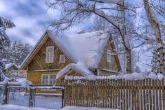 Hölzernes Häuschen schneebedeckt im Winter und in den Bäumen in den Schneefällen stockfotos