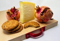 Hölzernes hackendes Brett mit Zusammenstellung von Käsen, Plätzchen und Granatapfel tragen Früchte für Lebensmittelkonzept Stockfotografie