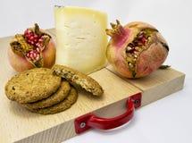 Hölzernes hackendes Brett mit Zusammenstellung von Käsen, Plätzchen und Granatapfel tragen Früchte für Lebensmittelkonzept Stockfoto