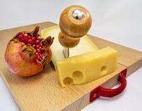 Hölzernes hackendes Brett mit Zusammenstellung von Käsen und Granatapfel tragen Früchte für Lebensmittelkonzept Stockfotografie