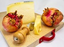 Hölzernes hackendes Brett mit Zusammenstellung von Käsen und Granatapfel tragen Früchte für Lebensmittelkonzept Lizenzfreie Stockfotografie