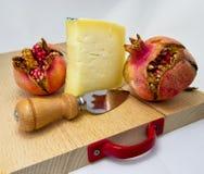 Hölzernes hackendes Brett mit Zusammenstellung von Käsen und Granatapfel tragen Früchte für Lebensmittelkonzept Lizenzfreie Stockbilder