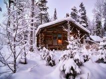 Hölzernes Haus abgedeckt durch einen Schnee in einem Wald stockfoto