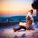 Hölzernes Haus abgedeckt durch einen Schnee in einem Wald Junge, Kind, das interessantes Buch zu seinem Freundschneemann am Hinte lizenzfreie stockfotografie