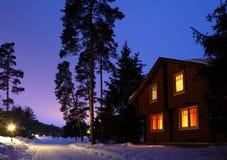 Hölzernes Haus im Holz in der Dämmerung Stockfotos