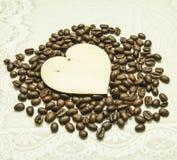 Hölzernes Herz auf dem Hintergrund von Kaffeebohnen Lizenzfreie Stockfotografie