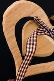 Hölzernes Herz auf einem Seil mit hölzernen Bällen, ein Bogen in der Mitte, s stockfotografie