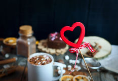 Hölzernes Herz auf einem Stock auf einem Hintergrund von Schalen mit Getränk choco Lizenzfreies Stockbild