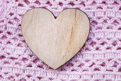 Hölzernes Herz auf Hintergrund der Rose strickte strukturiertes handgemachtes Produkt Stockfoto