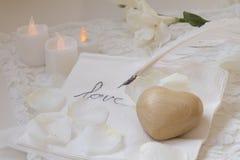 Hölzernes Herz, Gänsefeder, Kerzen und Blume stockbilder