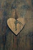 Hölzernes Herz mit einem Schlüssel auf Holz maserte Hintergrund Stockfoto