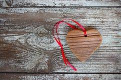 Hölzernes Herz mit rotem Band auf einem Holztisch Lizenzfreie Stockfotografie