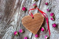 Hölzernes Herz mit rotem Band und kleinen getrockneten Rosebuds Lizenzfreie Stockfotografie