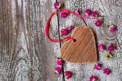 Hölzernes Herz mit rotem Band und kleinen getrockneten Rosebuds Stockfoto