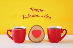 Hölzernes Herz nahe bei Kaffeetassen auf Holztisch Lizenzfreie Stockfotografie