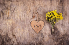 Hölzernes Herz und gelbe Blumen auf einem alten getragenen hölzernen Hintergrund Hintergründe und Beschaffenheiten Kopieren Sie P stockbilder