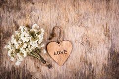 Hölzernes Herz und weiße Blumen auf einem alten hölzernen Brett Hintergründe und Beschaffenheiten St Valentinsgruß ` s Tag Lizenzfreie Stockfotos