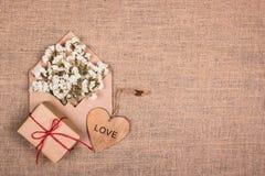 Hölzernes Herz, weiße Blumen in einem Umschlag und ein Geschenk Kopieren Sie Platz Stockfotografie