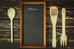 Hölzernes Küchenzubehör und Menütafel Lizenzfreie Stockfotografie