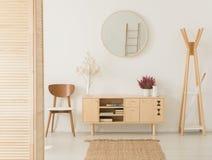 Hölzernes Kabinett mit Blumen zwischen stilvollem braunem Stuhl und hölzernem Aufhänger lizenzfreies stockfoto