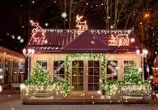 Hölzernes kleines Haus mit Dekoration des neuen Jahres in der Nacht Abstraktes Hintergrundmuster der weißen Sterne auf dunkelrote Stockfotografie
