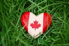 Hölzernes kleines Herz mit dem roten weißen kanadischen Flaggenahornblatt, das im Gras auf grünem Waldnaturhintergrund liegt Lizenzfreie Stockfotos