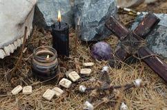 Hölzernes Kreuz, alte Runen, Pentagram und schwarze Kerzen Stockbild