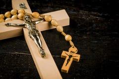 Hölzernes Kreuz auf alten Brettern mit einem Rosenbeet stockfotografie
