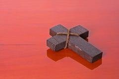 Hölzernes Kreuz auf einer hölzernen Tabelle Stockbilder