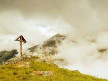 Hölzernes Kreuz an einer Bergspitze in der Alpe Lizenzfreies Stockbild