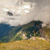 Hölzernes Kreuz an einer Bergspitze in der Alpe Kreuz auf einen Gebirgsgipfel, wie typisch in den Alpen Lizenzfreies Stockfoto